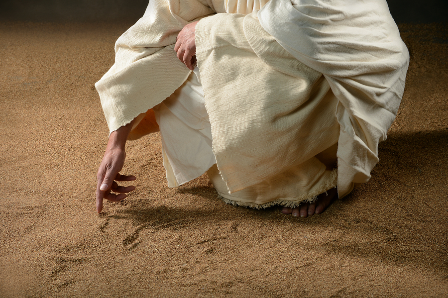 Jesus writing in the sand with finger