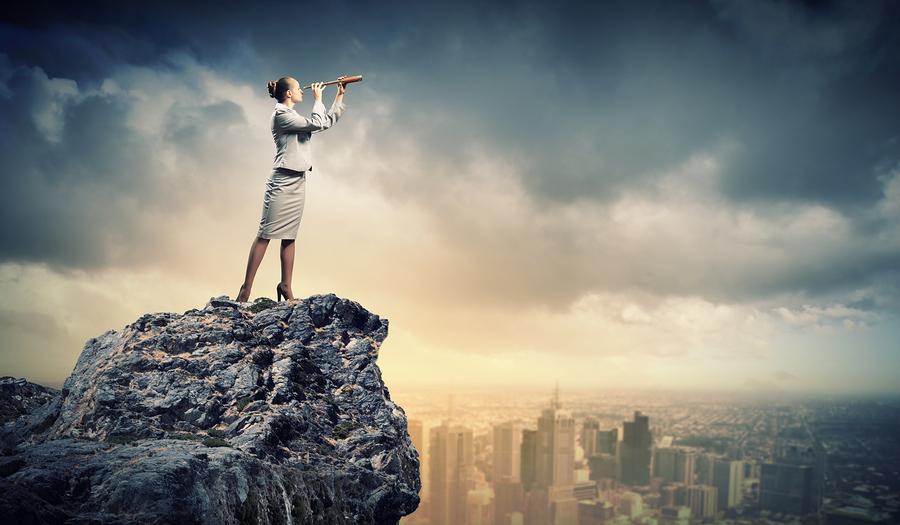 Image of businesswoman looking in telescope standing atop of roc