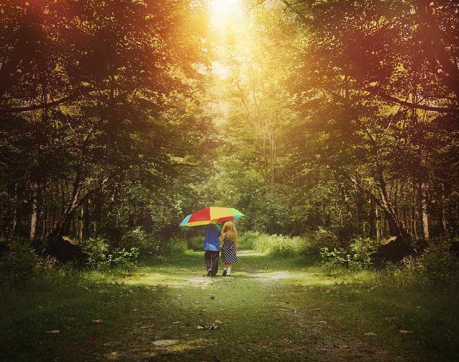 Two children are walking down a sunshine trail in the woods holding a rainbow umbrella for a friendship hope or happiness concept.
